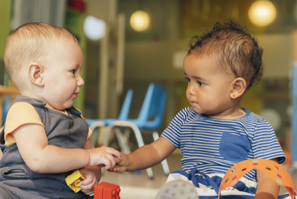Two babies holding hands playing magic